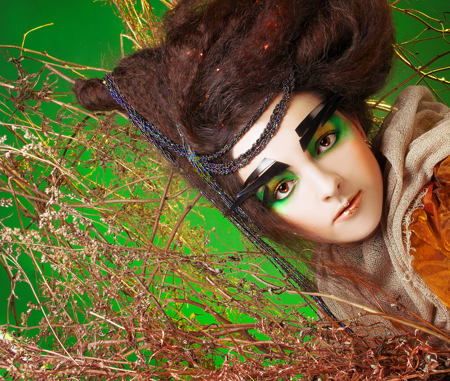 Fairy. Young woman with artistic make-up and hairstyle posing near golden twigs.