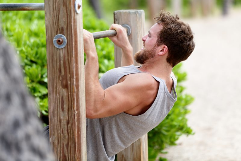 Pull-up strength training exercise - fitness man working out his