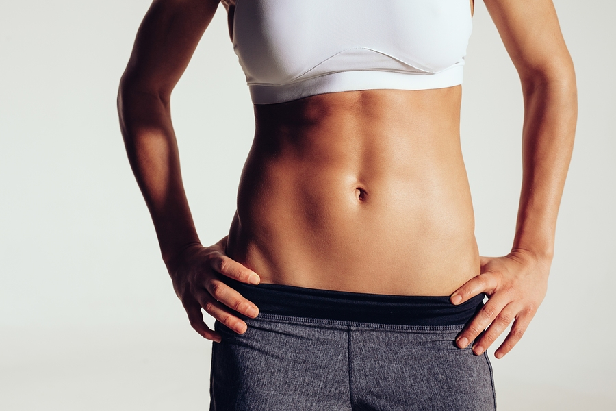 Close up of fit woman's torso with her hands on hips. Female with perfect abdomen muscles on grey background