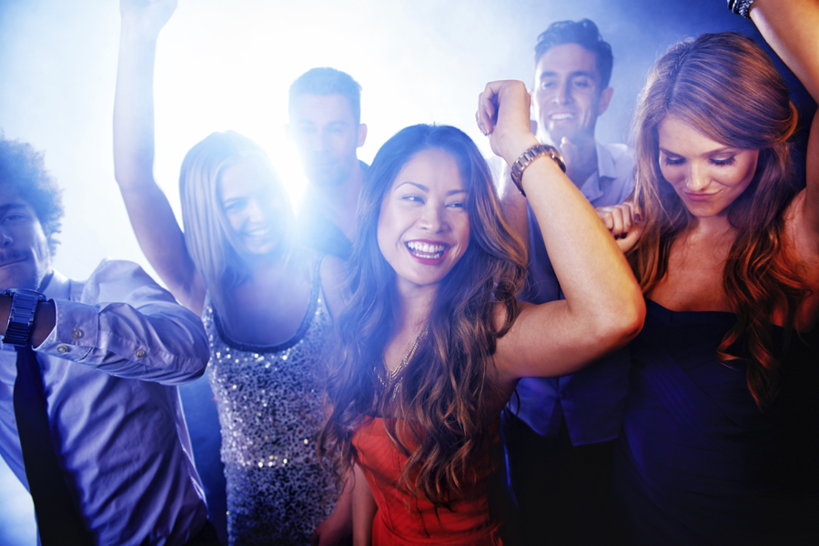 A group of young people dancing and letting loose at a nightclub